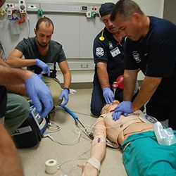 EMS professionals performing CPR on mannequin